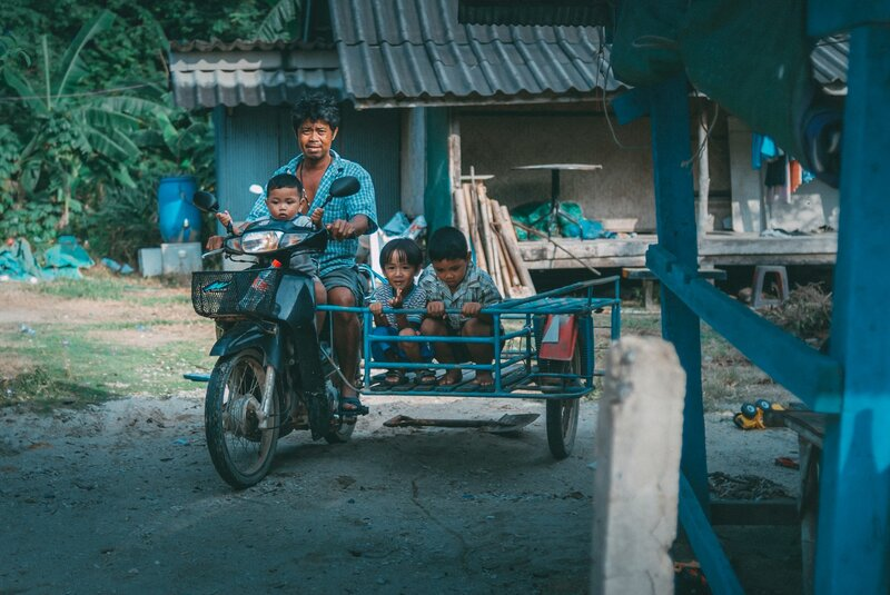 Father and his sons riding a scooter