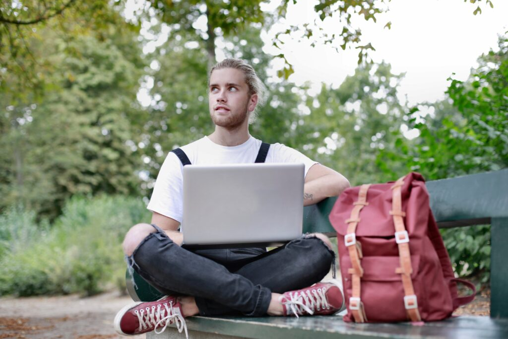 man-sitting-on-bench-with-his-laptop-3981543